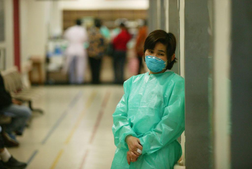 Một nhân viên bệnh viên mặc áo bảo hộ cùng khẩu trang để bảo vệ cô khỏi sự lây nhiễm virus SARS vào ngày 14/03/2003, ở Hong Kong.