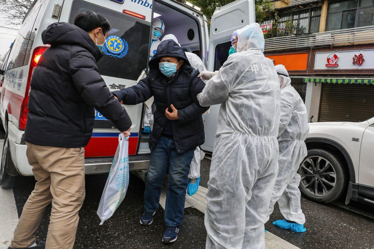 Một bệnh nhân được các nhân viên y tế hỗ trợ mặc quần áo bảo hộ khi anh ta ra khỏi xe cứu thương ở Vũ Hán, tỉnh Hồ Bắc của Trung Quốc, vào ngày 26/1/2020. (STR / AFP qua Getty Images)