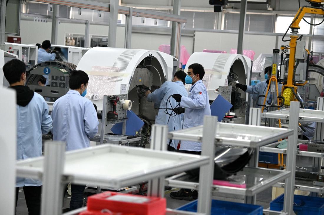 Nhân viên đeo khẩu trang bảo vệ làm việc tại nhà máy của Siemens, nơi lắp ráp thiết bị y tế tại Thượng Hải vào ngày 24/2/2020. (Ảnh của NOEL CELIS / AFP qua Getty Images)