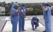 Các y tá tập trung tại sân đỗ trực thăng của bệnh viện để cầu nguyện cho bệnh nhân và gia đình trong bối cảnh dịch COVID-19 bùng phát