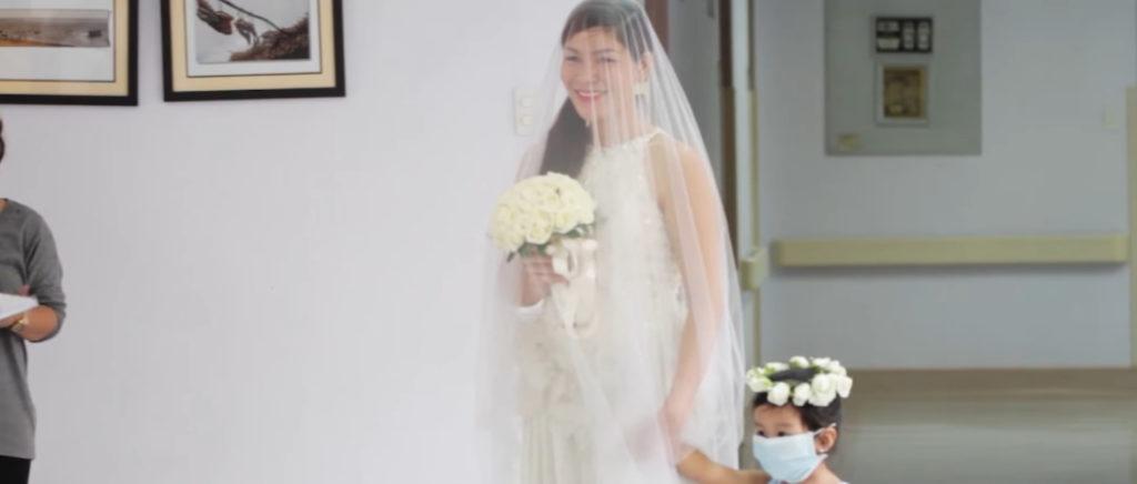 Leizel từ từ bước vào đầy thanh lịch trong bộ váy cô dâu cùng khăn trùm đầu.Con gái của cặp đôi cũng mặc một chiếc váy phù dâu, và đeo khẩu trang để bảo vệ cha bé. Em nắm chặt tay mẹ bước đến bên cha.