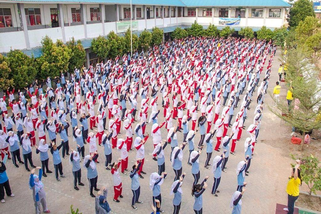 Khoảng 500 giáo viên và học sinh ở một trường trung học số 38 ở Batam, Indonesia đang luyện bài công pháp số 2 của Pháp Luân Công.