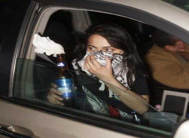 Ảnh chụp Urooj Rahman đang cầm bom xăng trên xe.