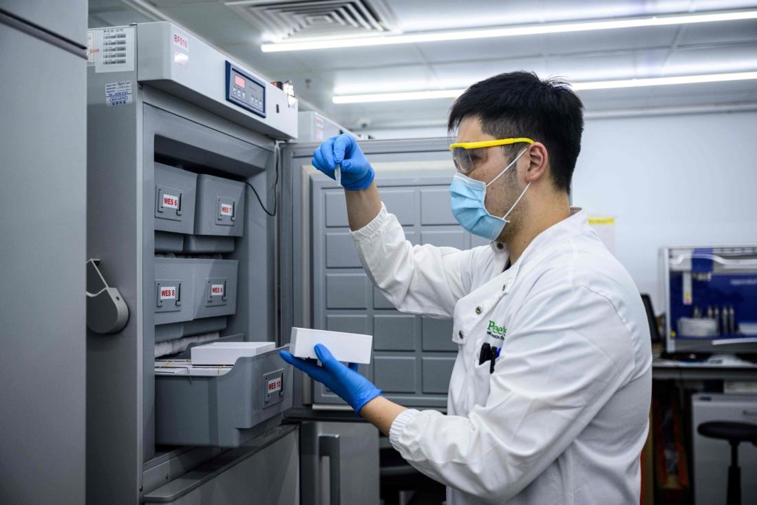 Ngày 5/6/2020, một nhân viên xử lý một mẫu xét nghiệm tại phòng thí nghiệm công nghệ sinh học mới Prenetic / Circle DNA Hong Kong. (Ảnh của ANTHONY WALLACE / AFP qua Getty Images)