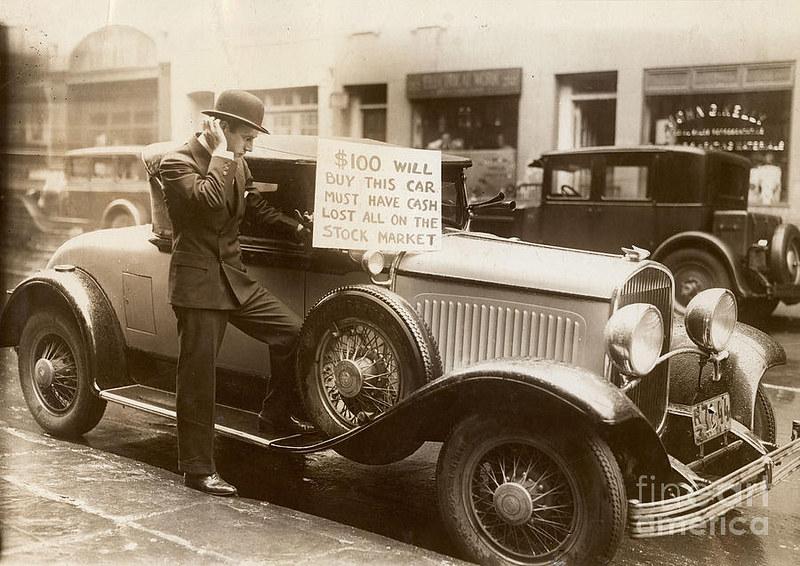 """Một người đàn ông bên chiếc xe hơi của mình với tấm biển """"Bán xe với giá 100 USD tiền mặt, đã mất tất cả tiền vào thị trường chứng khoán"""". (Ảnh: Flickr)"""