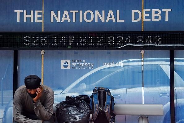 Một người đàn ông đợi ở trạm xe buýt hiển thị nợ quốc gia của Hoa Kỳ vào ngày 19 tháng 6 năm 2020 tại Washington, DC. (Ảnh của OLIVIER DOULIERY / AFP qua Getty Images)