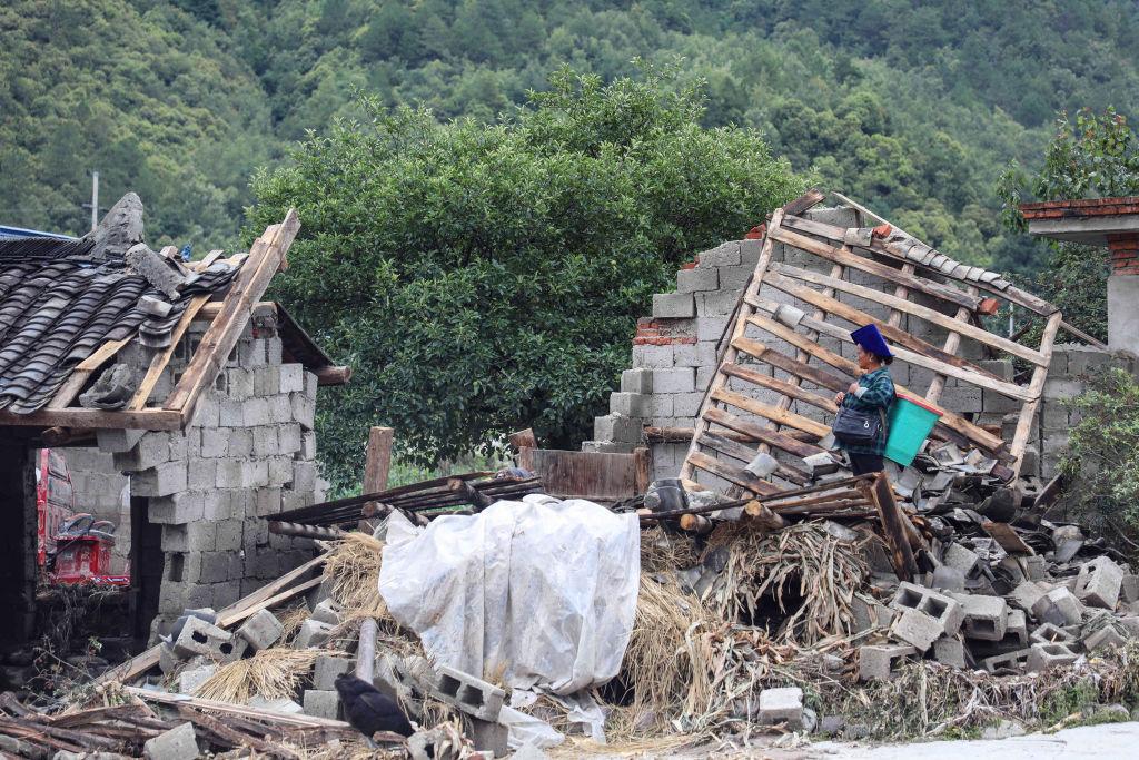 Một người phụ nữ đang đứng bên đống đổ nát do hậu quả của mưa lũ lịch sử ở Tứ Xuyên vào ngày 29/06/2020.