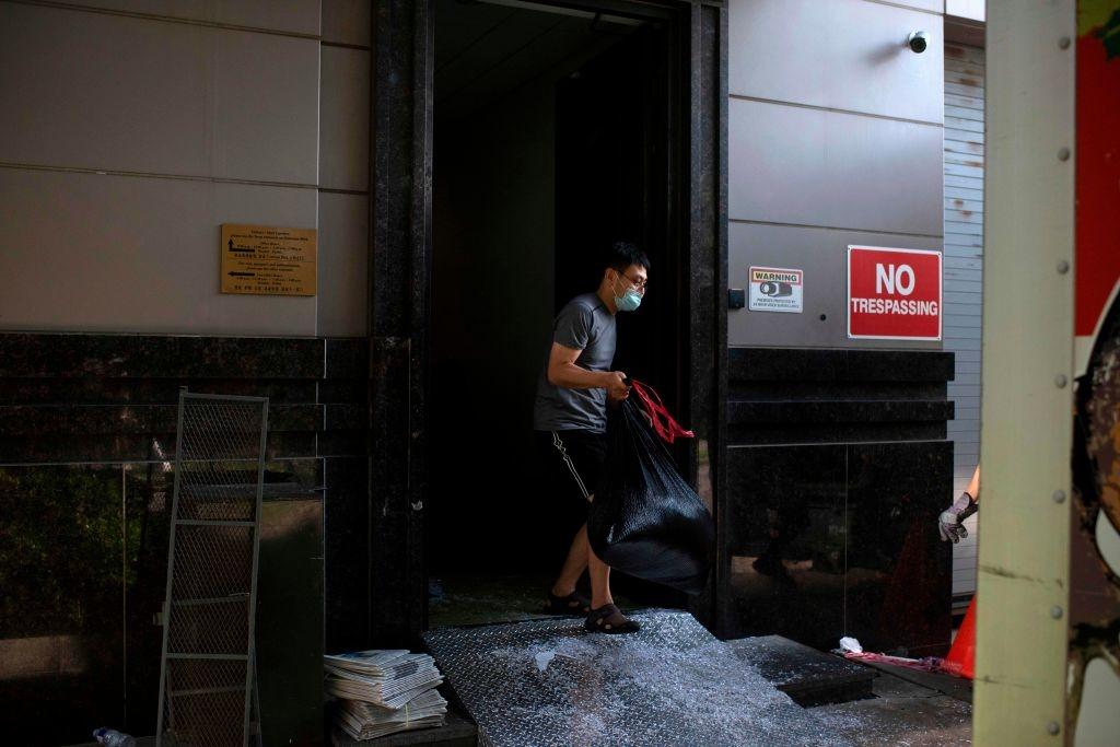 Một nhân viên lãnh sự quán Trung Quốc mang bao tải rác tài liệu đã bị xé vụn để tiêu hủy trước khi đóng cửa. (Ảnh: MARK FELIX/AFP /AFP via Getty Images)