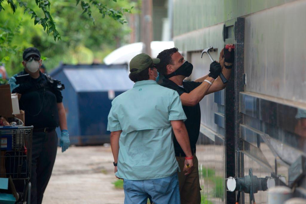 Các nhân viên thực thi pháp luật đang phá cửa sau của Lãnh sự quán Trung Quốc ở Houston sau khi hết hạn đóng cửa, rời đi. hôm 24/7. (Ảnh: MARK FELIX/AFP /AFP via Getty Images)