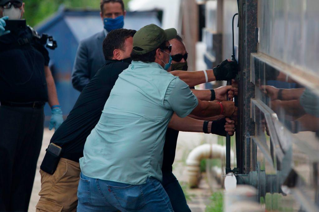 Các nhân viên thực thi pháp luật đang kéo cửa sau của Lãnh sự quán Trung Quốc ở Houston sau khi hết hạn đóng cửa, rời đi. hôm 24/7. (Ảnh: MARK FELIX/AFP /AFP via Getty Images)