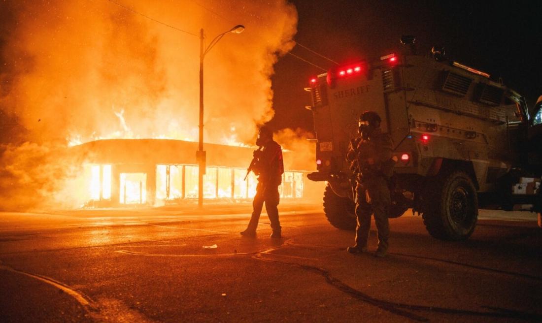 Một chiếc xe bọc thép của cảnh sát tuần tra một ngã tư, trong khi một tòa nhà bị đốt cháy bởi những kẻ bạo loạn ở Kenosha, Wis., vào ngày 24/8/2020. (Brandon Bell / Getty Images)