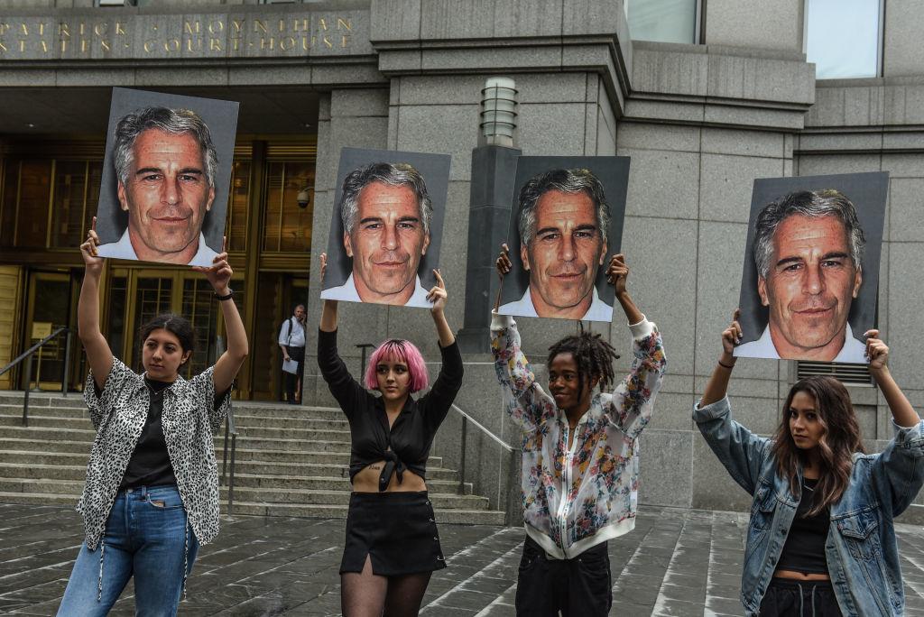 """Một nhóm biểu tình có tên """"Hot Mess"""" giơ bảng hiệu của Jeffrey Epstein trước tòa án Liên bang vào ngày 8 tháng 7 năm 2019 tại Thành phố New York. Theo báo cáo, Epstein sẽ bị buộc tội một tội buôn bán tình dục trẻ vị thành niên và một tội âm mưu tham gia buôn bán tình dục trẻ vị thành niên. (Ảnh của Stephanie Keith / Getty Images)"""