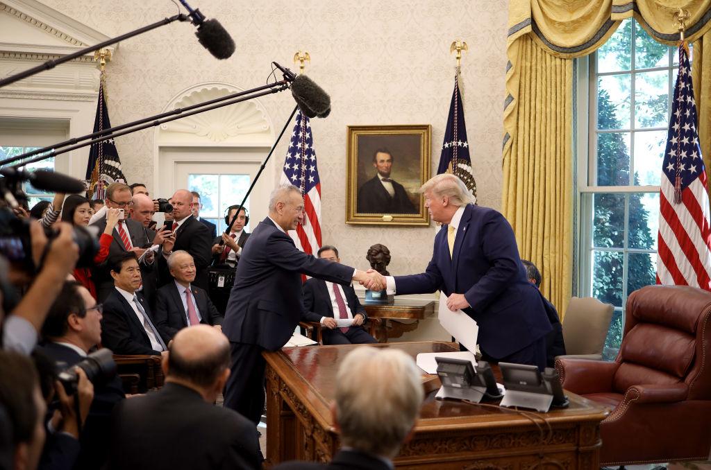 """Tổng thống Hoa Kỳ Donald Trump bắt tay với Phó Thủ tướng Trung Quốc Lưu Hạc sau khi công bố một thỏa thuận thương mại """"giai đoạn một"""" với Trung Quốc trong Phòng Bầu dục tại Nhà Trắng vào ngày 11 tháng 10 năm 2019 ở Washington, DC. (Ảnh của Win McNamee / Getty Images)"""