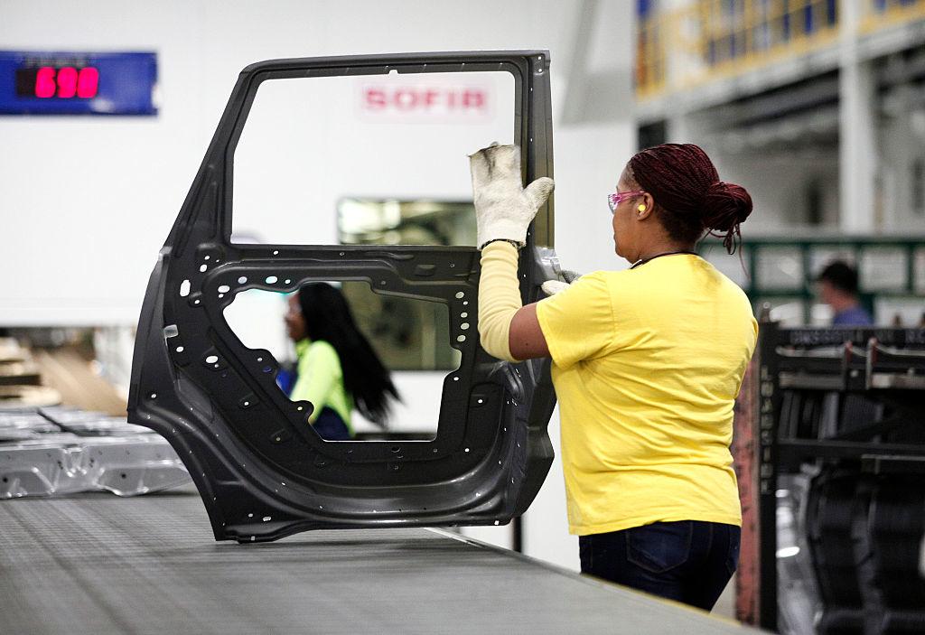 Một công nhân xử lý cánh cửa thoát ra từ máy ép mới trị giá 63 triệu đô la tại Nhà máy dập Fiat Chrysler Automobiles US Warren ngày 22 tháng 1 năm 2016 ở Warren, Michigan. (Ảnh của Bill Pugliano / Getty Images)