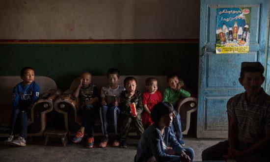 Trẻ em Duy Ngô Nhĩ xem một chương trình truyền hình vào buổi sáng của Lễ hội Corban ngày 12 tháng 9 năm 2016 tại huyện Turpan, thuộc tỉnh Tân Cương xa xôi, Trung Quốc (Ảnh của Kevin Frayer / Getty Images)