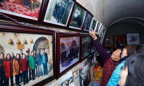 Bức ảnh được chụp vào ngày 22 tháng 10 năm 2016 cho thấy mọi người đang xem ảnh của Chủ tịch Trung Quốc Tập Cận Bình tại một ngôi nhà trong hang động nơi ông Tập sống khi còn trẻ, ở Liangjiahe, thuộc tỉnh Thiểm Tây, Trung Quốc (Ảnh: STR / AFP qua Getty Images)