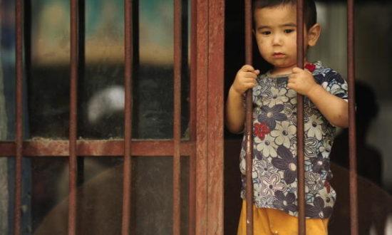 Một cậu bé người Duy Ngô Nhĩ nhìn ra từ nhà của mình ở khu vực người Duy Ngô Nhĩ ở thành phố Urumqi, vùng Tân Cương của Trung Quốc vào ngày 12 tháng 7 năm 2009. (Ảnh: PETER PARKS / AFP qua Getty Images)