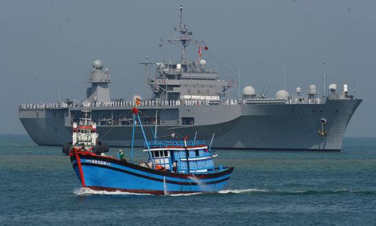 Một tàu đánh cá Việt Nam đi bên cạnh USS Blue Ridge hàng đầu của Hạm đội 7 của Hoa Kỳ vào cảng Tiên Sa vào ngày 23/4/2012 trong bối cảnh căng thẳng gia tăng ở Biển Đông giữa Việt Nam và Trung Quốc (Ảnh: HOANG DINH NAM / AFP qua Getty Images)