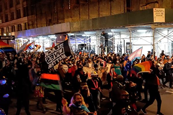 Vào tối ngày 5/11/2020, những người biểu tình da đen tuần hành với lá cờ Black Lives Matter trên tay. (Ảnh Epoch Times)