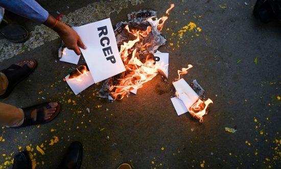 Một người biểu tình đốt biểu ngữ trong cuộc biểu tình phản đối kế hoạch của chính phủ tham gia Hiệp định Đối tác Kinh tế Toàn diện Khu vực (RCEP), tại New Delhi vào ngày 4 tháng 11 năm 2019. (Ảnh của Sajjad HUSSAIN / AFP / Getty Images)