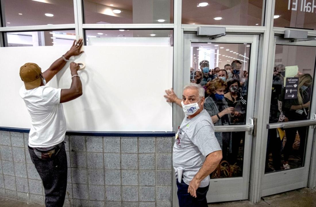 Nhân viên phòng phiếu dán bảng trắng lên các cửa sổ của khu vực kiểm phiếu tại Trung tâm TCF ở Detroit vào ngày 4/11/2020. (Seth Herald / AFP qua Getty Images)