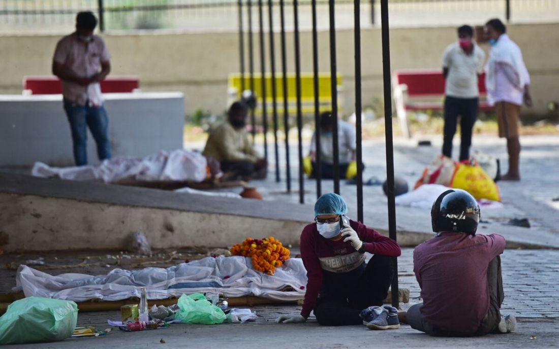 Người thân ngồi cạnh thi thể nạn nhân COVID-19 đã chết tại một lò thiêu điện thành phố ở Allahabad, Ấn Độ, vào ngày 22/4/2021. (Sanjay Kanojia / AFP qua Getty Images)