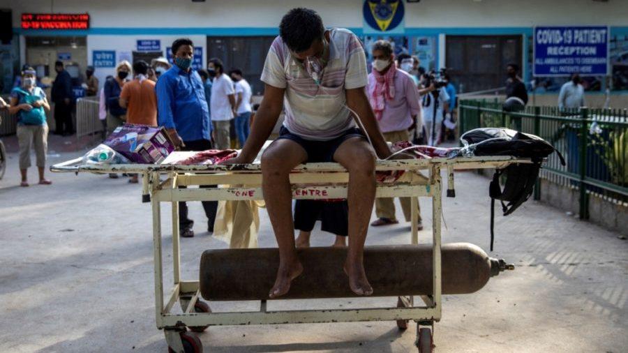 Một bệnh nhân ở thủ đô New Delhi đang ngồi trên cáng thở oxy chờ tới lượt được nhập viện hôm 23/4. Người dân Ấn Độ liên tục xếp hàng dài bên ngoài các bệnh viện, chờ được y bác sĩ tiếp nhận để điều trị Covid-19.