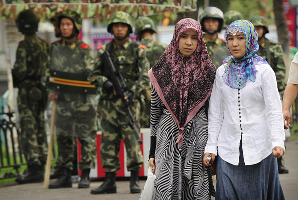 Hai người phụ nữ Duy Ngô Nhĩ đi qua chốt kiểm tra của cảnh sát Trung Quốc đứng gác bên ngoài Grand Bazaar ở quận Duy Ngô Nhĩ, thành phố Urumqi, Tân Cương, Trung Quốc vào ngày 14/7/2009. (PETER PARKS / AFP qua Getty Images)