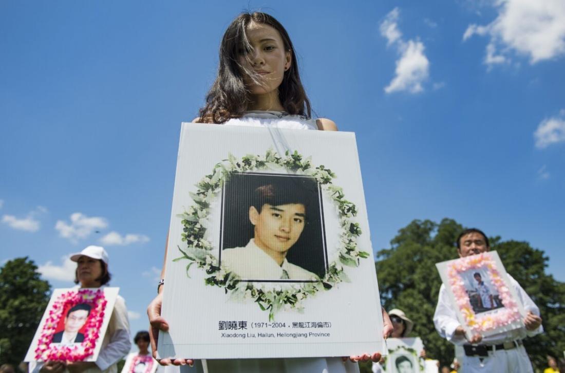 Các học viên Pháp Luân Công (Pháp Luân Đại Pháp) cầm ảnh tưởng niệm các nạn nhân trong cuộc bức hại tà ác của ĐCSTQ đối với các học viên của pháp môn, tại Đồi Capitol ở Washington, vào ngày 17/7/2014. (Jim Watson / AFP / Getty Images)