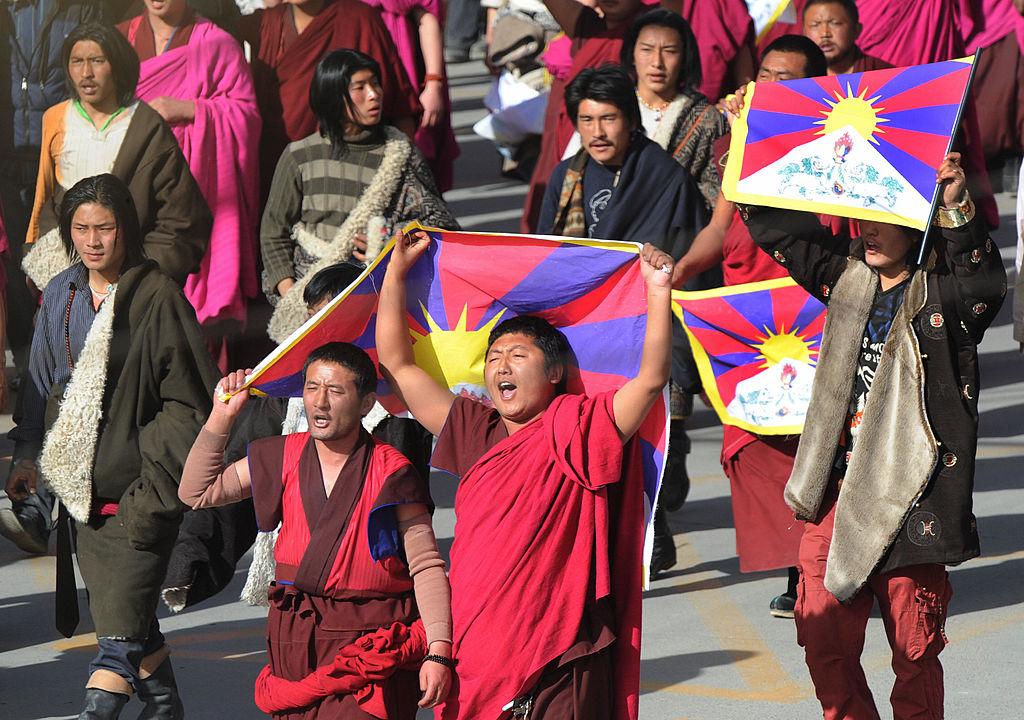 Những người biểu tình dẫn đầu bởi các nhà sư Phật giáo Tây Tạng hô khẩu hiệu và mang theo quốc kỳ Tây Tạng sau khi bị cảnh sát chống bạo động chặn lại tại một cuộc biểu tình gần Tu viện Labrang lịch sử, chỉ đứng sau Cung điện Potala ở Lhasa, ở thị trấn Xiahe, tỉnh Cam Túc, vào ngày 14/3/2008. Các cuộc biểu tình diễn ra trùng với một tuần biểu tình chống lại sự cai trị của ĐCSTQ bên trong Tây Tạng, bắt đầu bằng các cuộc biểu tình đánh dấu kỷ niệm một cuộc nổi dậy thất bại năm 1959 của người Tây Tạng. (Mark Ralston / AFP qua Getty Images)