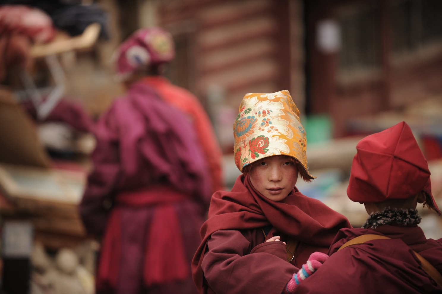 Bức ảnh chụp ngày 4/4/2013 này cho thấy một nữ tu sĩ Phật giáo tập sự đi qua Tu viện Seda, trường Phật giáo Tây Tạng lớn nhất trên thế giới, có tới 40.000 tăng ni cư trú trong một số thời điểm trong năm. Seda, được người Tây Tạng gọi là Serthar nằm ở quận Ganzi ở phía tây tỉnh Tứ Xuyên của Trung Quốc và đã trở thành tâm điểm của các cuộc biểu tình và bạo lực kể từ cuộc nổi dậy của người Tây Tạng vào tháng 3/2008. Hơn 110 người Tây Tạng đã xuống đường từ năm 2009, trong đó hầu hết đã chết vì những thương tổn họ phải chịu, trong các cuộc biểu tình chống lại cái mà họ coi là sự đàn áp của ĐCSTQ. Tuy nhiên, Bắc Kinh bác bỏ những cáo buộc này và nhắc đến những đầu tư đáng kể vào Tây Tạng và các khu vực khác có đông dân cư Tây Tạng. Mặc dù vậy, các nhà phê bình khẳng định, đi kèm với sự phát triển kinh tế là một làn sóng Hán hóa các dân tộc thiểu số, và làm xói mòn văn hóa truyền thống của Tây Tạng. (PETER PARKS / AFP qua Getty Images)