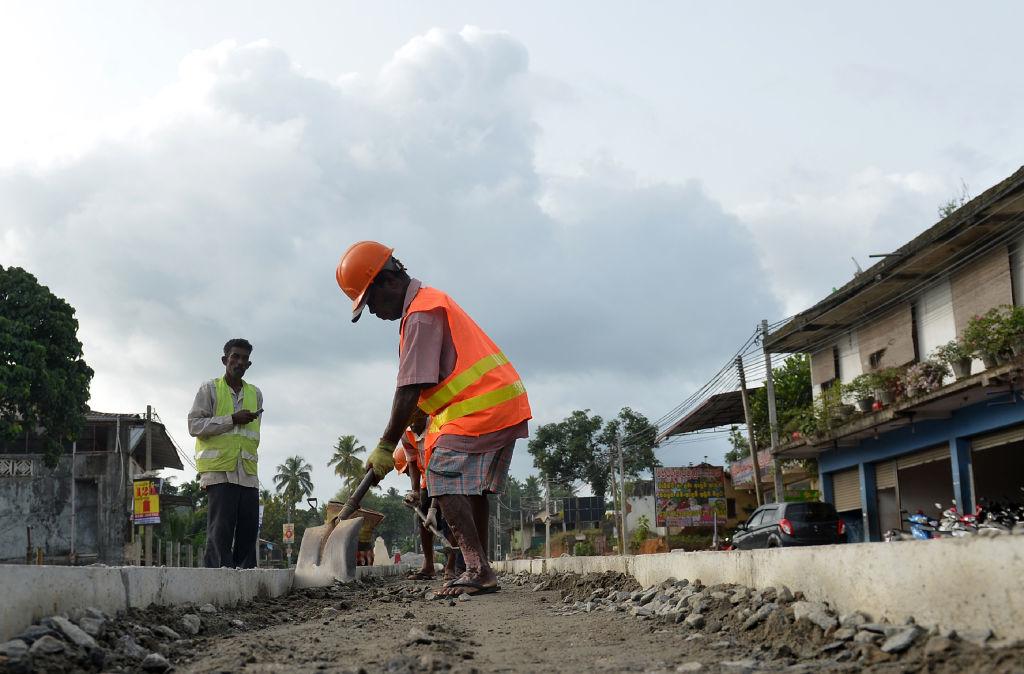 Các công nhân xây dựng đường bộ Sri Lanka làm việc dọc theo một con đường ở Colombo hôm 05/08/2018. Ngân hàng trung ương Sri Lanka vào ngày 3 tháng 8 thông báo họ đã có được bảo đảm khoản vay 1 tỷ USD của Trung Quốc khi hòn đảo, một mắt xích chính trong Sáng kiến Vành đai và Con đường đầy tham vọng của Bắc Kinh, phát triển quan hệ chặt chẽ hơn với nền kinh tế lớn nhất Á Châu . (Ảnh: Larkruwan Wanniarachchi / AFP / Getty)